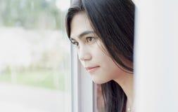 Profiel van tienermeisje het kijken uit venster Stock Afbeelding