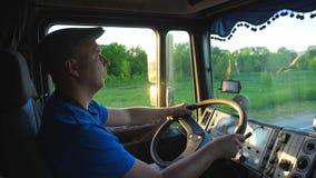 Profiel van vrachtwagenbestuurder het berijden door platteland in avond Mens in hoed die zijn vrachtwagen controleren en van reis stock video