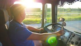 Profiel van vrachtwagenbestuurder het berijden door platteland in zonsondergangtijd Mens in hoed die zijn vrachtwagen controleren stock footage