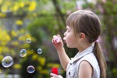 Profiel van vrij klein peuter blond meisje die met grappige ernstige uitdrukking kleurrijke transparante zeepbels in openlucht op Royalty-vrije Stock Afbeelding