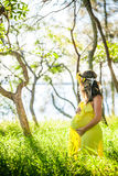 Profiel van zwangere vrouw met lang haar in gele kleding in Royalty-vrije Stock Afbeeldingen