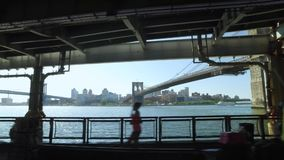 Profielmening die op de Rivier Bikeway van het Oosten met de Brug van Brooklyn in Afstand berijden stock videobeelden
