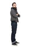 Profielmening van de gebaarde mens die jasje over sweatshirt met een kap met gekruiste wapens dragen die camera bekijken Royalty-vrije Stock Afbeeldingen