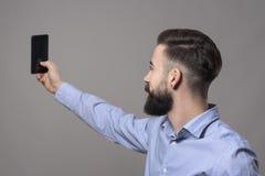 Profielmening van de jonge moderne knappe gebaarde bedrijfsmens die selfie foto met smartphone nemen stock afbeeldingen