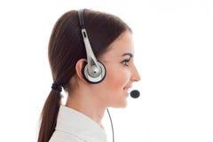 Profielportret van het aantrekkelijke donkerbruine die meisje van de call centrearbeider met hoofdtelefoons en microfoon op wit w Royalty-vrije Stock Foto