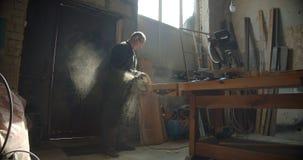 Profielschot van hogere mannelijke meester die bij vervaardiging werken die de houten raad malen die worden geconcentreerd stock videobeelden