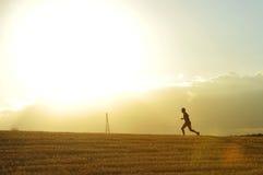 Profielsilhouet die van de jonge mens in platteland lopen die dwars de joggingdiscipline van het land in de zomerzonsondergang op Royalty-vrije Stock Afbeeldingen