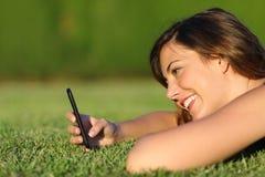 Profil śmieszna dziewczyna używa mądrze telefon na trawie Fotografia Stock