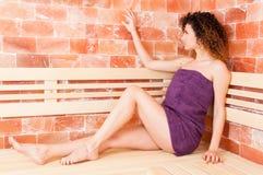 Profil atrakcyjny kobiety obsiadanie i mienie ręka na ścianie Obrazy Royalty Free