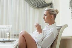 Profil av den attraktiva unga blondinen som dricker kaffe Arkivbild
