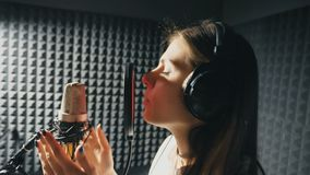 Profil av den härliga flickan som sjunger i solid studio Ung kvinnlig sångare som antecknar känslomässigt ny sång Kvinnan sjunger stock video