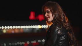 Profil av den nätta ensamma brunettflickan på en nattgata som ler och skrattar stock video