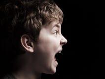 Profil av den ropa pojken Arkivfoto