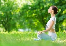 Profil av den sportive kvinnan, i att göra en gest för zen för lotusblommaposition Royaltyfria Bilder