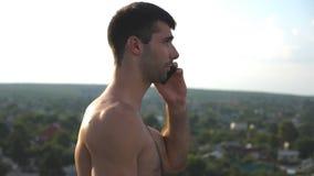 Profil av den stiliga mannen som talar på mobiltelefonen med cityscape på bakgrund Ung grabb som talar på den utomhus- smartphone lager videofilmer