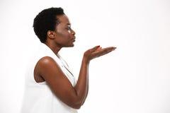 Profil av den unga kvinnan för charmig afrikansk amerikan som överför en kyss Arkivbilder