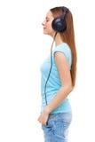 Profil av den unga kvinnan med hörlurar som lyssnar till musik Royaltyfri Bild