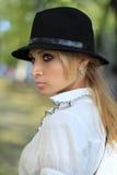Profil av en flicka i svart hatt Arkivbild