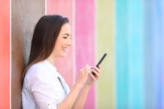 Profil av en flicka som använder den smarta telefonen i en färgrik gata royaltyfri foto