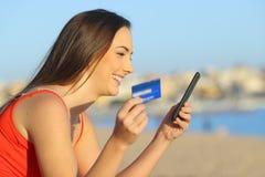 Profil av en flicka som direktanslutet betalar med en smart telefon royaltyfria bilder