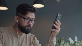 Profil av en hållande ögonen på video för ung man på en smartphone i ett kafé lager videofilmer