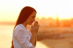 Profil av en koncentrerad kvinna som ber på solnedgången royaltyfri foto