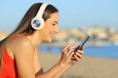 Profil av en kvinna som lyssnar till musik genom att anv?nda mobiltelefonen arkivfoto