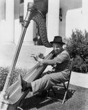 Profil av en man som spelar en harpa och le (alla visade personer inte är längre uppehälle, och inget gods finns Leverantörgarant Royaltyfria Foton