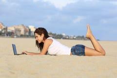 Profil av en tonåringflicka som bläddrar hennes bärbar dator som ligger på sanden av stranden Royaltyfri Fotografi