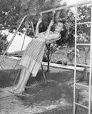 Profil av en ung kvinna som svänger på en gunga i en trädgård (alla visade personer inte är längre uppehälle, och inget gods finn Arkivfoton