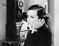 Profil av en ung kvinna som talar på en payphone (alla visade personer inte är längre uppehälle, och inget gods finns Leverantörb Royaltyfri Foto