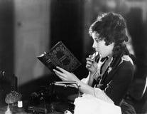 Profil av ett sammanträde för ung kvinna och läsning en bok och äta (alla visade personer inte är längre uppehälle, och inget god arkivfoto