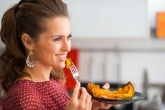 Profil av kvinnainnehavtuggan av grillad pumpa på en gaffel Arkivfoton