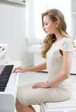 Profil av kvinnan som spelar pianot arkivfoto