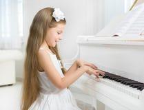 Profil av lilla flickan i den vita klänningen som spelar pianot royaltyfri fotografi