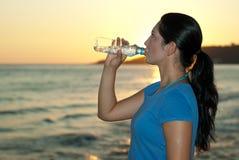 Profil d'eau potable de femme sur la plage photos libres de droits