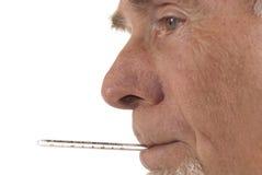 Profil d'homme aîné avec le thermomètre dans son mout Image stock