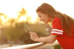 Profil d'un ado tenant un téléphone intelligent dans un balcon Photo stock