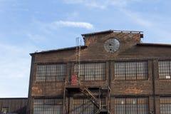 Profil d'un bâtiment industriel abandonné, fenêtre circulaire dans la façade de brique photo libre de droits