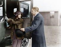 Profil d'un homme aidant une jeune femme à monter à bord d'une voiture (toutes les personnes représentées ne sont pas plus long v Image libre de droits