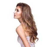 Profil d'une belle femme avec de longs cheveux onduleux et maquillage Photographie stock libre de droits