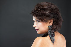 Profil d'une femme avec de beaux cheveux et boucles d'oreille noires chics étendues images stock