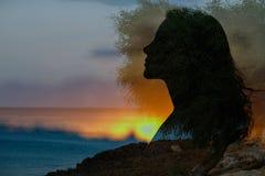 Profil d'une fille sur le fond de la mer et du coucher du soleil, silho image libre de droits