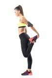 Profil de femme sportive faisant la jambe étirant l'exercice de quadriceps sur la jambe simple Images libres de droits