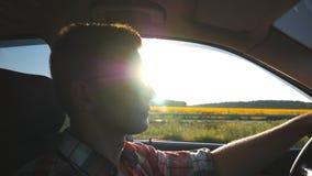 Profil de jeune homme dans des lunettes de soleil conduisant une voiture avec la fusée du soleil au fond Type beau conduisant l'a clips vidéos