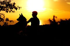 Profil de silhouette du chien de berger allemand reposant avec obéissance tout près son homme de propriétaire, garçon marchant su images stock