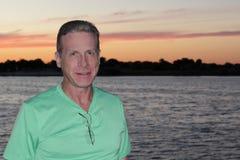 Profil de sourire d'homme avec le lac sunset Photos stock