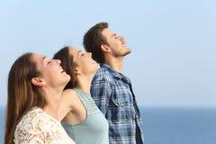 Profil de trois amis respirant l'air frais sur la plage images libres de droits