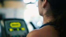 Profil der Frau ausarbeitend auf elliptischer Maschine an der Turnhalle stock footage