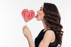 Profil der verlockenden attraktiven Frau, die Herz leckt, formte Lutscher Stockfotografie